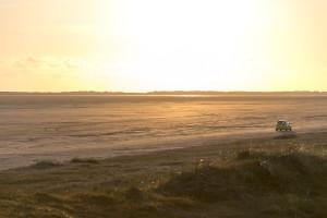 Auto auf dem Strand beim Sonnenuntergang