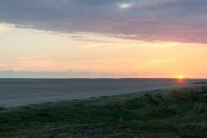 Blick über den Strand zur verschwindenen Sonne