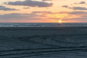 Sonne verschwindet in Wolken und Nordsee
