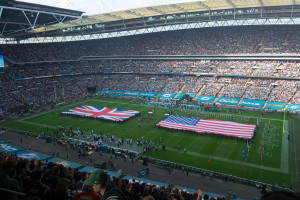 Bereit für die Nationalhymne mit großen Flaggen von USA und UK auf dem Spielfeld