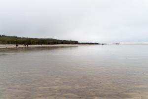 Strand so weit das Auge reicht, Ebbe und etwas Wasser auf dem Sand