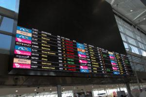 Sehr bunte Abflugtafel Sydney Flughafen