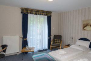 Zimmer im Hotel Wittorf, unten links ist das Baby Bett zu erahnen. Hinter der Scheibe ist ein kleiner Balkon.